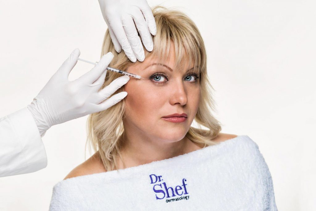 Image of hands injecting botox into woman's face