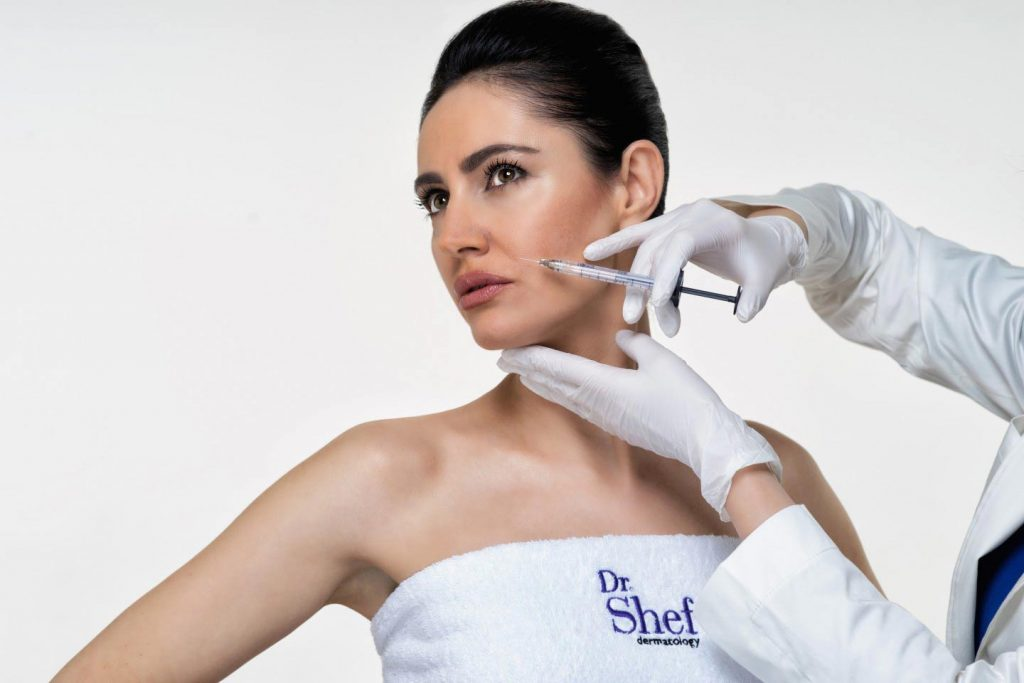 Image of hands injecting hyaluron filler into woman's face